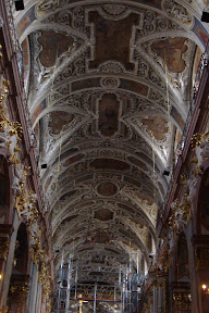 High ceilings.  Baroque-style ornaments.  Scaffolding.