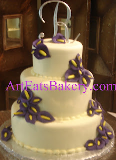 Three tier yellow fondant elegant romantic wedding cake with purple edible sugar flowers and monogram topper