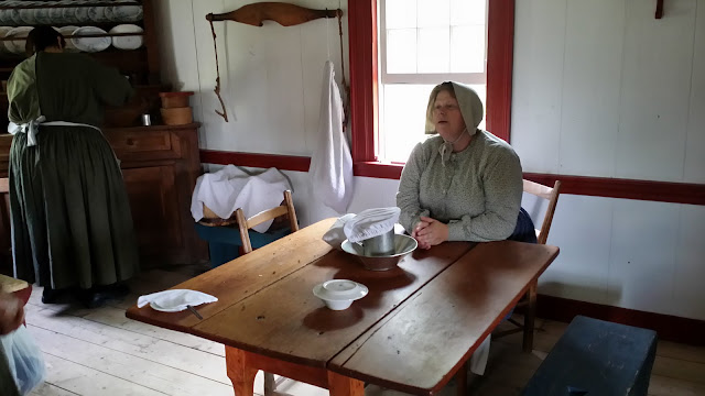 Here, the women were making bread. Notice the dishes covered with cloths or other dishes - to keep out the bugs? Acadian Historical Village, New Brunswick