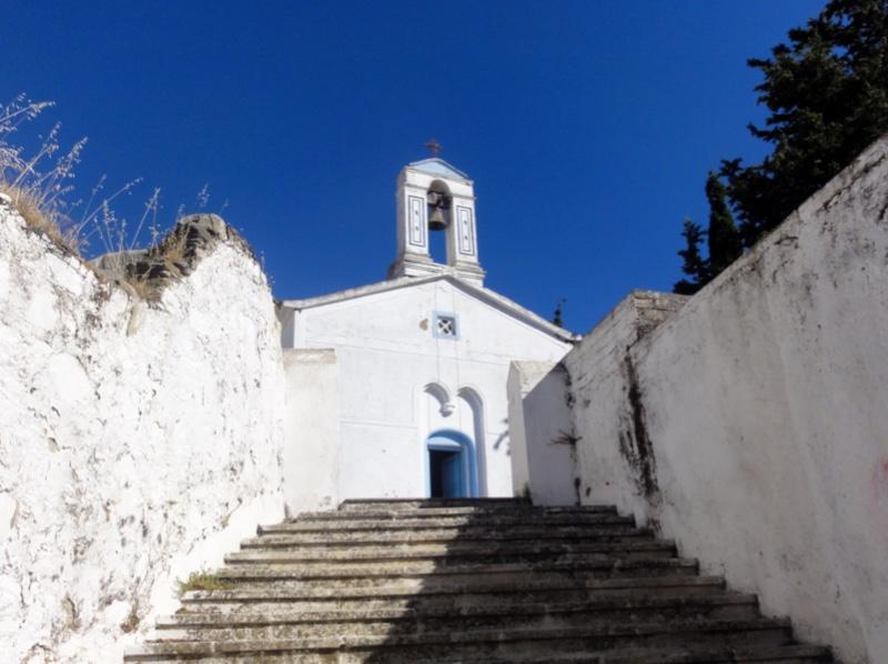 En liten, hvit kirke med klokke på toppen, øverst i en trapp med høye, hvite murer langs siden.