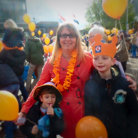 Picture of Catie with her 2 sons on Kings day. sons wearing orange crowns and carrying orange balloons