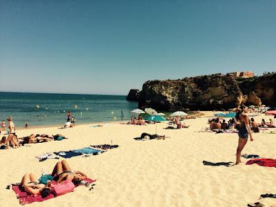 En sandstrand med blått hav og noen klipper i bakgrunnen.