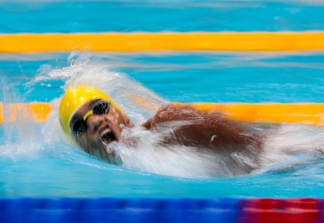 Wendell Belarmnino de óculos e touca amarela. O nadador está com a cabeça acima da água, virada para o lado para respirar