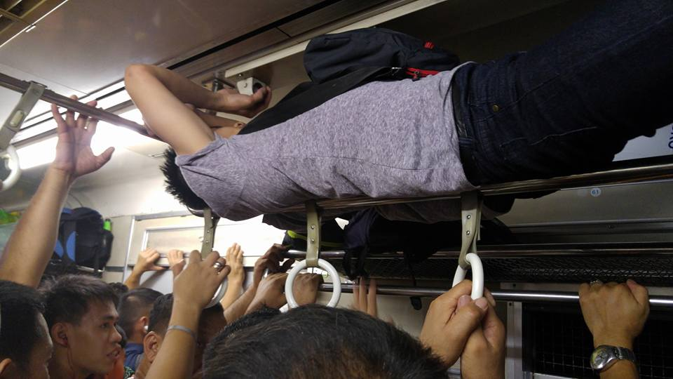 Image of One of these trains daily traveler made his own solution to stay out of tight space by climbing up the handrails up to the luggage compartment and BOOM, it's bedtime! I mean, NO, the guy laid down there in the luggage compartment for the rest of his journey.