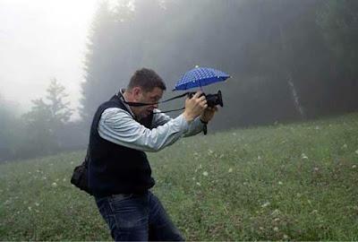 orang membawa kamera dilindungi payung kecil memotret ditengah hujan