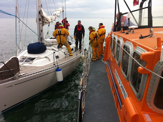 8 April 2012: Crew Member Rich Skerman aboard yacht and Tyne class lifeboat alongside. Photo: RNLI Poole Dave Riley