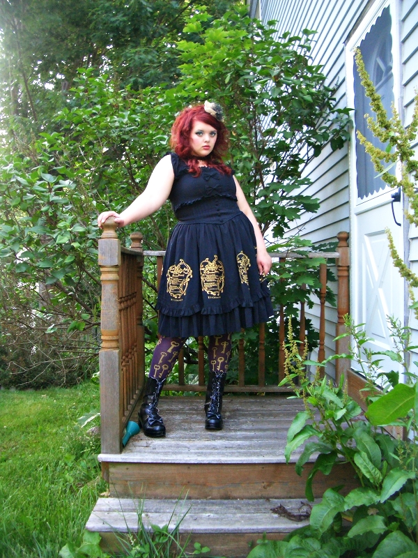 A fat, pale-skinned young woman with elaborately curled red hair stands on a set of steps adjacent to a side door. She is outside and surrounded by green-leafed trees and bushes. She is wearing a black dress that has decorative buttons lining the bodice, gold embroidery along the edge of the skirt, and a chiffon ruffle. On her legs are purple tights with gold keys and black boots with bows. On her head she wears a gold and black fascinator.