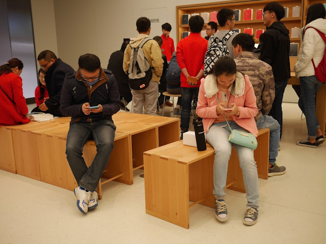 people using mobile phones at the SM Lifestyle Center Apple Store in Xiamen, China