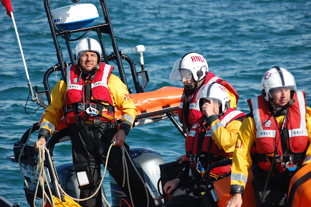 21 August 2011 - Helmsman Richard Skerman getting ready to throw a tow rope to the all-weather lifeboat, with Crew Member Mark Ponchard at the helm. Photo: RNLI Poole/Dave Riley