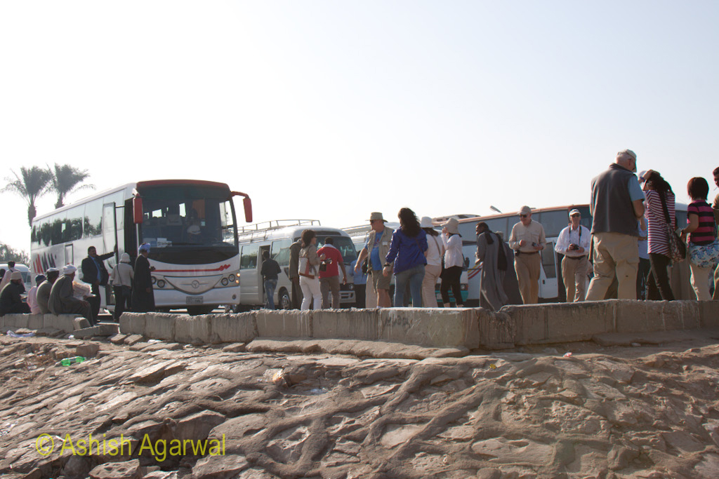 Tourist buses with a number of tourists at the Colossi of Memnon, outside Luxor, in Egypt