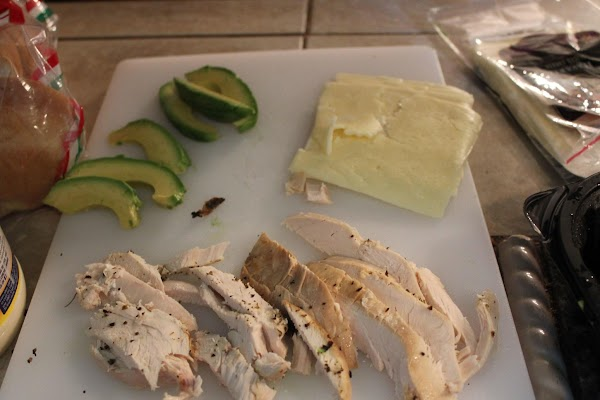 Slice up one-half of an avocado. Separate your cheese, then start slicing chicken breast...