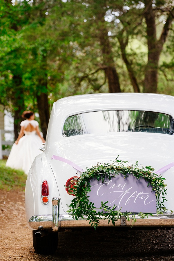 Purple wedding getaway car sign with white calligraphy and greenery garlands