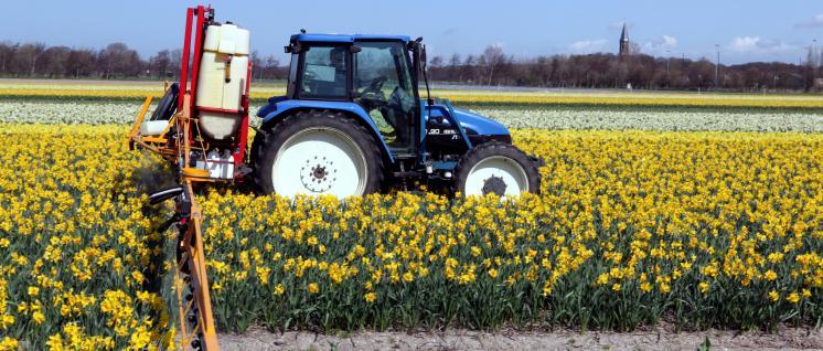 Traktor mit angedockter Sprühvorrichtung im Feld.