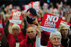 People against coal exports hold up signs during the Longview Coal Exports Hearing.