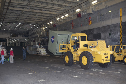 A forklift is used to carry ground support equipment into the well deck of the USS Anchorage at Naval Base San Diego.