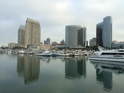 Høye bygninger bak et stille vann.