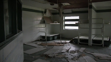 Photo: Prisoner room.  The ceiling is collapsing onto the floor where the inmates used to sleep.