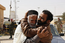 A rebel fighter (R) hugs a refugee fleeing unrest in Libya at the southern Libyan and Tunisian border crossing of Dehiba April 22, 2011. Thousands of people have fled worsening violence in Libya's Western Mountains region over the last week through the bo