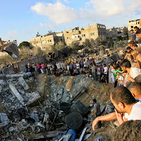 Palestinians gather around the rubble of a building where at least 20 members of the Al Najar extended family were killed by an Israeli strike in Khan Younis, in the southern Gaza Strip, Saturday, July 26, 2014. At least 20 members of an extended family, including at least 10 children, were killed by tank fire that hit a building on the edge of town, said Palestinian health official Ashraf al-Kidra. A brief cease-fire Saturday in the Gaza war between Israel and Hamas militants allowed thousands to return home to see the destruction. (AP Photo/Eyad Baba)
