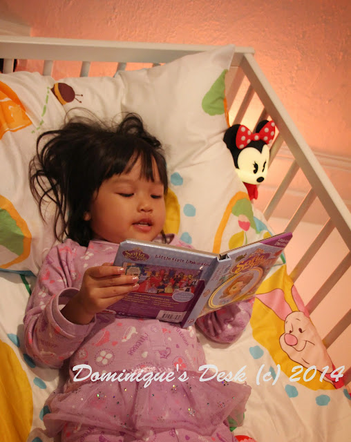 Tiger girl all cozy in bed reading with Minnie Mouse