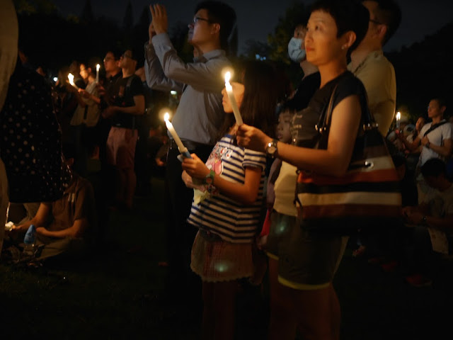 woman and girl holding candles at a vigil in Victoria Park, Hong Kong, commemorating the anniversary of the Tiananmen Square crackdown