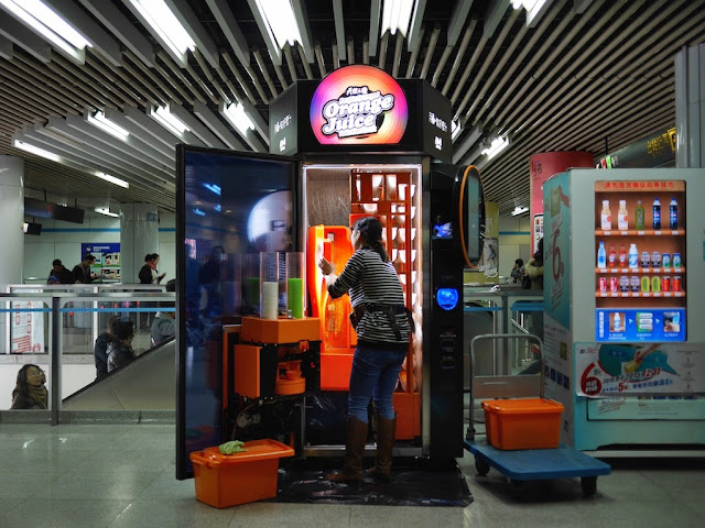 woman cleaning a fresh orange juice machine in a Shanghai metro station