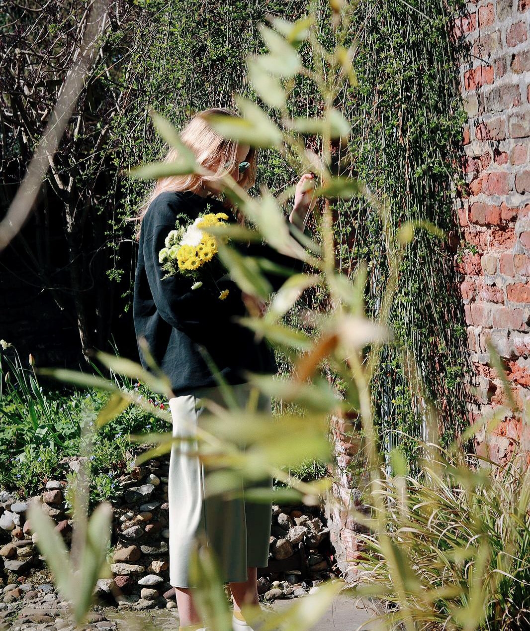 Amy is standing in an overgrown garden, hidden behind some greenery, holding a bunch of flowers in one arm