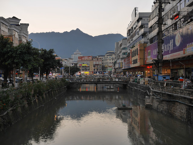 a Chinese city scene with a mountain in the background