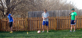 it's a pretty stupid game: we stand on one side of the lawn and kick the ball at a bottle on the other side
