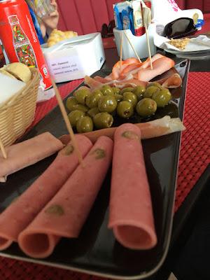 Et brett med sammenrullet kjøtt og oliven.