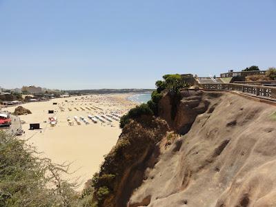 Utsikt fra en klippe ned mot en lang og bred strand.