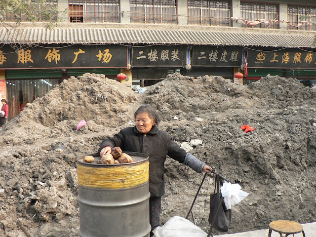 woman selling tubers next to a road construction site at the Shangqiu Ancient City