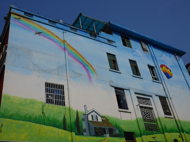 building with a painted rainbow, blue sky, birds, and a countryside house with a real blue sky in the background