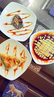 Clockwise desserts at DarSalam you see Baklava, a Date Roll and a dessert called Dark & Honey
