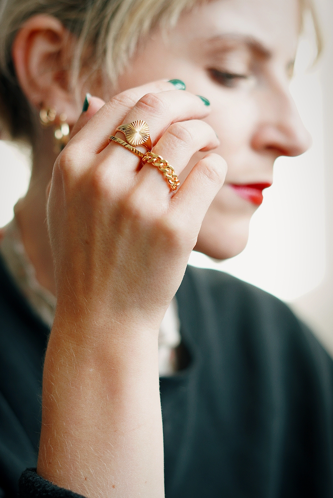 Amy's hand is in focus in front of her face which is not, on her hand are three gold rings; one chain linked, one plain band and one signet ringAmy's hand is in focus in front of her face which is not, on her hand are three gold rings; one chain linked, one plain band and one signet ring. She has green nail varnish on.
