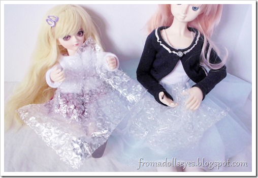 Ball jointed dolls playing with bubble wrap.