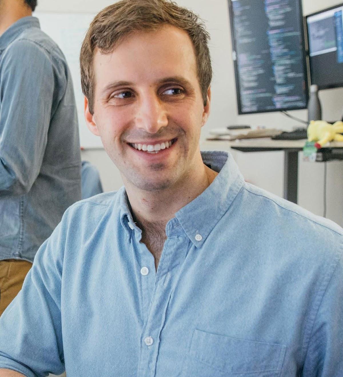 Troy Astorino, cofundador e diretor de tecnologia da PicnicHealth, conversa com um colega de trabalho enquanto outro colaborador trabalha no computador atrás dele.