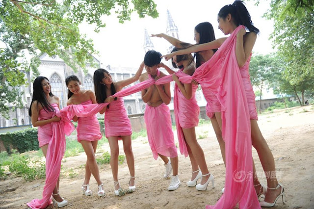 "six young women wearing pink dress holding a large pink ""ribbon"" which is wrapped around a young man's neck"