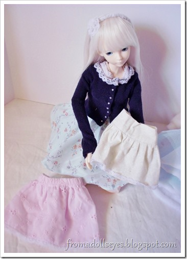 Sorting through pretty doll clothes.