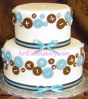 Two tier white fondant unique custom baby shower cake with blue and brown edible buttons and ribbon borders