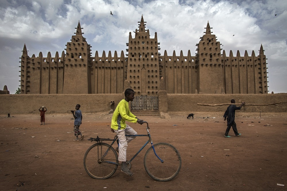 A boy rides a bicycle in front of the Great Mosque of Djenné. Photo credit: Marco Dormino/Flickr
