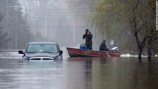 Two men pass a submerged truck in Gatineau, Quebec, on 8 May 2017. Photo: Adrian Wyld / The Canadian Press / AP