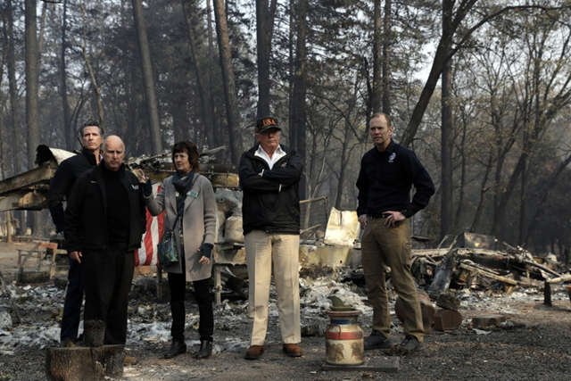 Trump visits a a neighborhood destroyed by the wildfires in Paradise, California, on Saturday, 17 November 2018. From left: Governor-elect Gavin Newsom, California Governor Jerry Brown, Paradise Mayor Jody Jones, Trump, and FEMA Administrator Brock Long. Trump denied any connection between global warming and the California wildfires, saying 'I want great climate, we're going to have that.' Photo: Evan Vucci / AP Photo