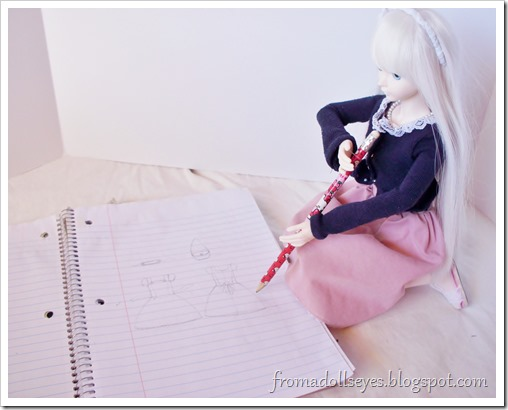 A ball jointed doll drawing with a large pencil.