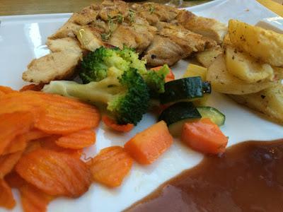 Tynnskåret kyllingkjøtt med broccoli, skiver av gulrøtter og saus i forgrunnen.