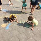 Mensen tekenen met krijt op de speelplaats met 1ABC