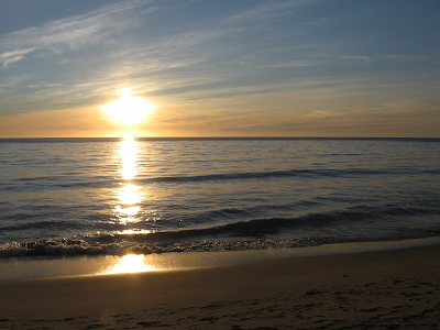 Sunrise over water and a beach.