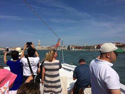 Mennesker foran på en båt. Venezia kan sees i bakgrunnen.