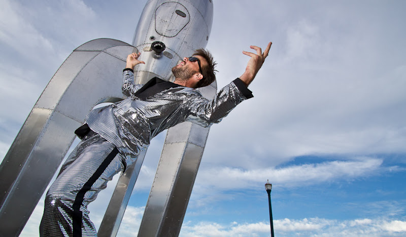 Disco Tux bill arches back in front of rocket statue
