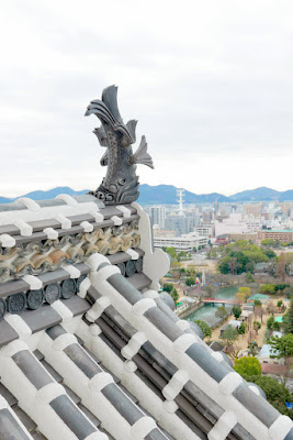View from a window at Himeji Castle, Japan. The fish statues you see are spiritual measure for the prevention of fires and these mythical tiger-headed fish are called kinshachi